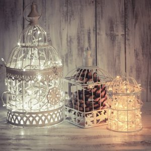 Christmas light decoration in a white bird cage.