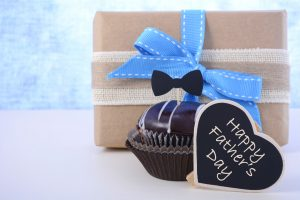 Happy Fathers Day cupcake gift on pale blue and white wood background.