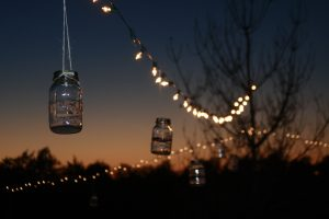 a summer evening lit with white lights and mason jars hanging